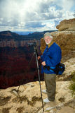 Senior Man Stands on the North Rim of the Grand Canyon Taking Pi Royalty Free Stock Image