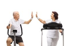 Senior man on a stationary bike and a senior woman on a treadmill high-fiving each other stock photography