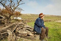 Senior man with stick outdoors. Senior man with stick sitting on firewood outdoors royalty free stock photos