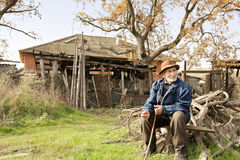 Senior man with stick sitting outdoors. On firewood heap against old house royalty free stock image