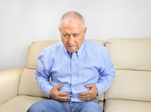 Senior man with stomachache. Senior man suffering stomach ache sitting on a couch in the living room at home Stock Image