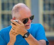 Senior man strains to hear phone stock photo