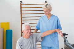 Senior man stretching with his therapist Stock Photo