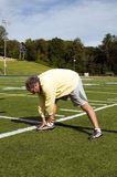 Senior man stretching sports field Stock Photo