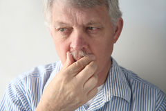 Senior man strokes his mustache Stock Photo
