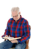Senior man studding the bible. A white hair senior citizen sitting in an old armchair with his glasses and Royalty Free Stock Photography