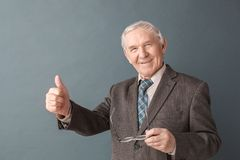 Senior man studio standing isolated on gray holding glasses showing thumb up positive royalty free stock photo
