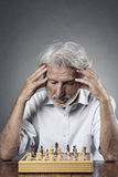 Senior man studying the chessboard Royalty Free Stock Image