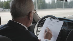 Senior man is studying documents while sitting in the car. Busy businessman. stock footage