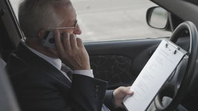 Senior man is studying the documents and talking on the phone while sitting in car. Busy businessman. stock footage