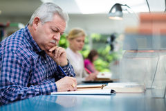 Senior man studying among young people in library stock image