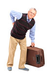 Senior man suffering from a back pain. Full length portrait of a senior man lifting his luggage and suffering from a back pain  on white background Royalty Free Stock Photography