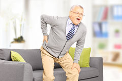 Senior man suffering from back pain. At home Stock Photos