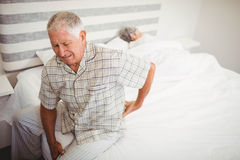 Senior man suffering from backache sitting on bed Stock Photo