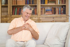 Senior man suffering from chest pain in living room Royalty Free Stock Image