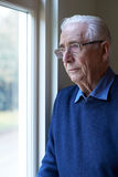 Senior Man Suffering From Depression Looking Out Of Window. Senior Man Suffering With Depression Looking Out Of Window stock images