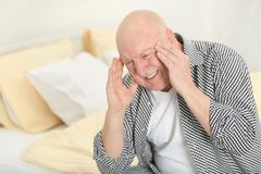 Senior man suffering from headache. At home Royalty Free Stock Images