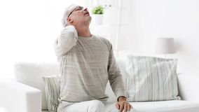 Senior man suffering from headache at home 106. Health care, pain, stress, age and people concept - senior man suffering from headache at home stock video