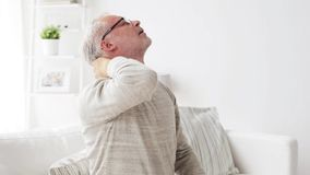 Senior man suffering from headache at home 30. Health care, pain, stress, age and people concept - senior man suffering from headache at home stock video