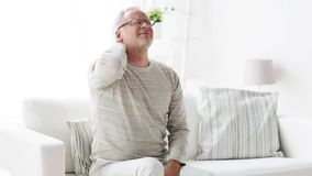 Senior man suffering from headache at home 105. Health care, pain, stress, age and people concept - senior man suffering from headache at home stock footage
