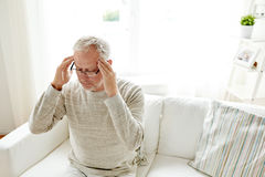 Senior man suffering from headache at home Stock Photography