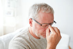 Senior man suffering from headache at home Stock Image