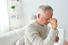 Senior man suffering from headache at home Stock Photo