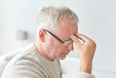 Senior man suffering from headache at home Royalty Free Stock Photos