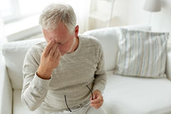 Senior man suffering from headache at home. Healthcare, pain, stress, age and people concept - senior man suffering from headache at home Royalty Free Stock Images