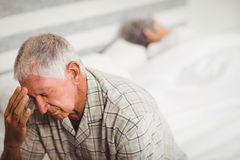 Senior man suffering from headache. Senior men in bedroom suffering from headache Stock Photos