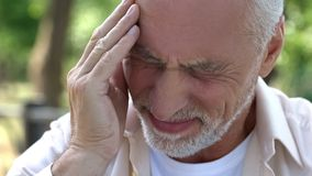 Senior man suffering headache, migraine attack during walk, risk of thrombus. Stock photo royalty free stock photography
