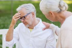 Senior man suffering from headache outdoors. Health, stress, old age and people concept - senior men suffering from headache outdoors Royalty Free Stock Image