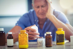 Senior man suffering from headache with prescription bottle Royalty Free Stock Image
