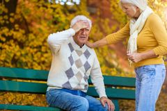 Senior man suffering from a headache, senior woman comforts him stock images
