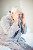 Senior man suffering from headache while sitting on bed Stock Photos