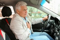 Senior man suffering from heart attack. In car stock photo
