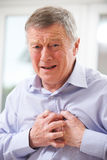 Senior Man Suffering Heart Attack At Home Royalty Free Stock Photography