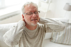 Senior man suffering from neckache at home Royalty Free Stock Photos