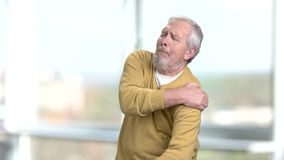 Senior man suffering from shoulder pain. Elderly man rubbing his shoulder on blurred background. Arthritis and sickness concept stock video