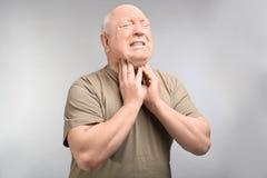 Senior man suffering from sore throat. On light background. Enduring pain Stock Photo