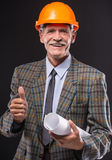 Senior man. In suit and helmet is holding draft royalty free stock image