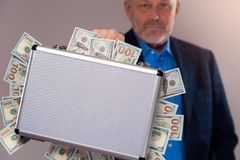 Senior man in suit holding case with dollar bills. Portrait of senior confident man in suit holding metal briefcase with dollar bills. Rich pensioner with cash royalty free stock image