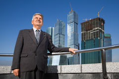 Senior man in suit near skyscrapers construction Royalty Free Stock Photography