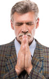 Senior man. In suit is praying and keeping eyes closed on white background royalty free stock image