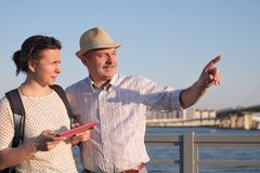 Senior man in summer hat shows the way on the map to young woman. royalty free stock photos