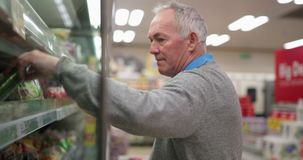 Senior man in the supermarket. Senior man is buying fruit and vegetables in the supermarket stock footage