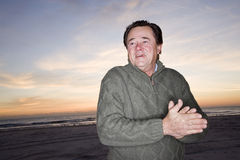 Senior man in sweater at dawn on beach Royalty Free Stock Photo