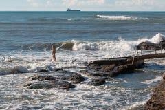 Senior man with swim cap prepares to swim in rough sea, cargo sh. Ip in background Stock Photo