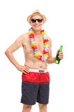 Senior man in a swim trunks holding a beer Stock Photography