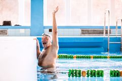 Senior man swimming in an indoor swimming pool. Active pensioner enjoying sport Stock Photography